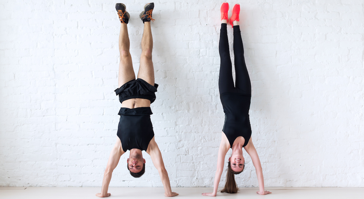 Athletes doing handstands on white wall